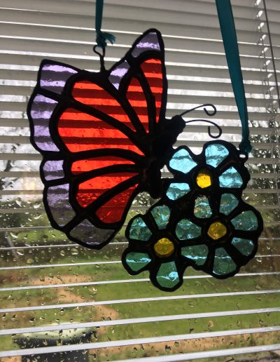 Stained glass butterfly on forget-me-not sun catcher
