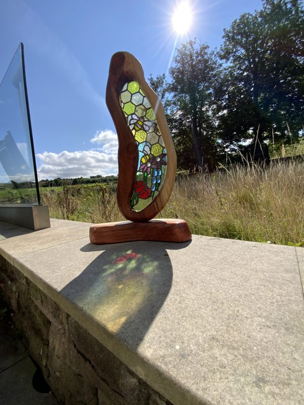 Stained glass and wood bee and flower sculpture
